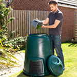 A straight customer emptying a kitchen caddy into a garden compost bin