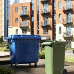 A green wheelie bin and a four wheeled bin outside a block of flats