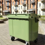 A green four wheeled bin in-situ outside