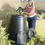 A women adding kitchen waste from a caddy into a garden compost bin
