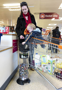 A mother with her child in a supermarket trolly. The child is adding batteries to a battery tube.