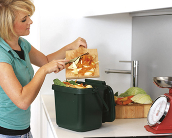 A women placing food waste from her chopping board into her kitchen caddy.