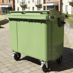 A green four wheeled bin outside in-situ