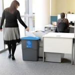 An office bin with a blue lid with a large slot for paper in use in an office