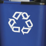 A close up of the recycle graphic on the side of a blue deskside bin