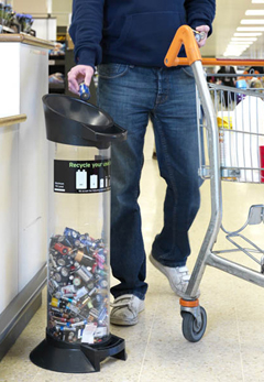 A man at a supermarket adding batteries to a battery recycling tube