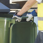 A green wheelie bin being collected