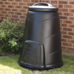 A black compost converter in a garden