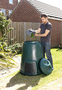 A man adding the contents of his kitchen caddy into his compost bin.