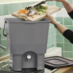 Food waste being added to a kitchen composter from a wooden chopping board on a kitchen counter