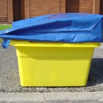A side view of a blue bag acting as a lid for a large yellow kerbside box