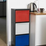 A recycling system stacked vertically with three drawers in a kitchen