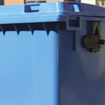 A close up of a blue four wheeled bin