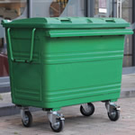 A green four wheeled bin outside a restaurant