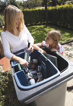 Mother and daughter adding recycling to inner caddy inside wheelie bin