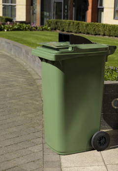 A green wheelie bin with a special opening so the public can drop waste into it without raising the lid