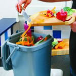 Food waste being scooped into a kitchen caddy with a large aperture