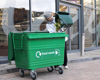 A cheif emtying food waste from a kerbside caddy into a four wheeled bin labelled food waste