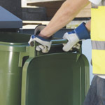 A bin man holding a wheelie bin via its hange handle