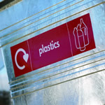 Custom graphics with the word 'plastics' written on a silver four wheeled bin