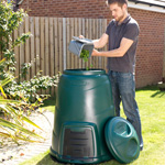 A man emptying his kitchen caddy into a garden compost bin