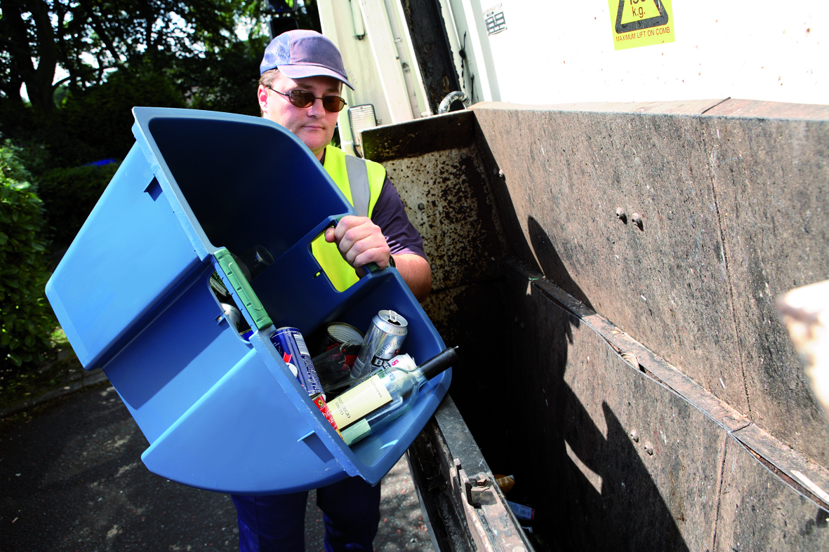 A bin man tipping an inner caddy into a waste truck