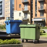 A green and blue four wheeled bin outside a block of flats