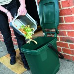 A man emptying a 5 litre silver kitchen caddy into his kerbside caddy