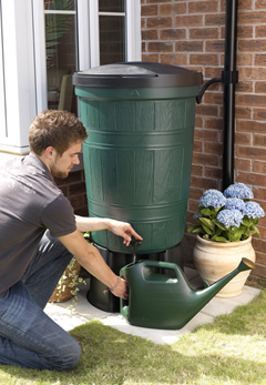 A Gardener filling a watering can with a Garden Lake Water butt