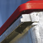 A close up of a silver four wheeled bin with a red lid