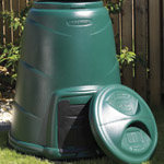 A greeen compost converter with its lid placed nex to it