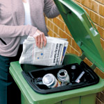A women accessing the main area of the wheelie bin through a gap at the side of the inner caddy