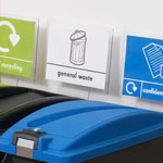 A range of signs on top of three EcoSort bins to distinguish what should be recycled in each.