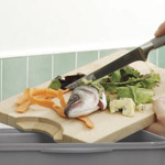 Food waste being added to a kitchen composter from a wooden chopping board