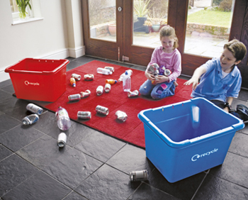 Two children recycling cans and bottles with two recycling boxes