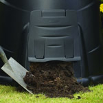 A shovel scooping out compost from a under a compost converters hatch