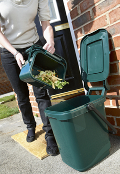 A women adding her kitchen caddy waste into a kerbside caddy for pickup