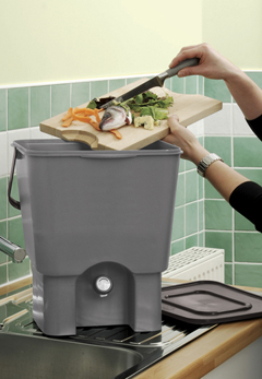 A women emtying food waste into a kitchen composter