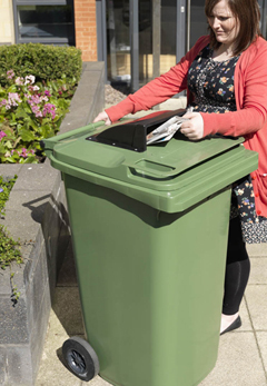A women placing a newspaper into a customised hatch in the top of a green wheelie bin