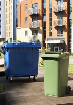 A four wheeled and two wheeled wheelie bin next to each other outside