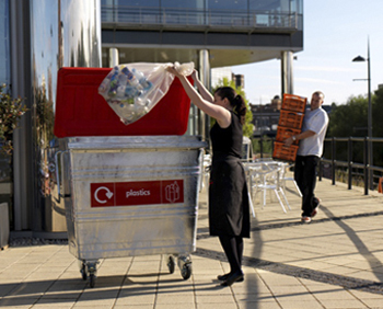 A rubbish bag filled with plastic bottles being placed into a silver four wheeled bin