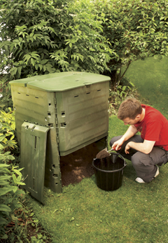 A man scooping out compost from a large green Thermo King composter.