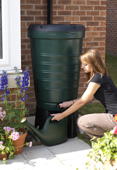A gardener getting water out of a 190 litre water butt.