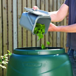 A women adding food scraps into the top of a green compost converter