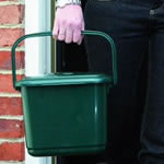 A kitchen caddy being taken outside using its handle