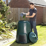 A man tipping the contents of his kitchen caddy into a garden compost converter