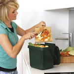 A women filling her kitchen caddy with vegetable peelings