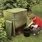 A man scooping compost from the base of his garden compost bin