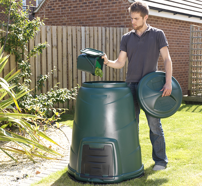 A man adding the contents of his kitchen caddy into a garden compost bin